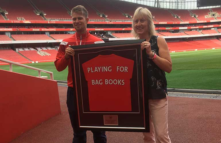 Luke presents our Storytelling Manager, Nina Martinez, with a shirt worn by an Arsenal player.